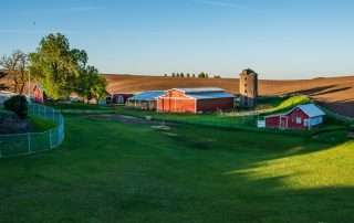 farm with rolling hills and a red barn